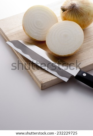 fresh onions cut on the chopping board with knife - stock photo