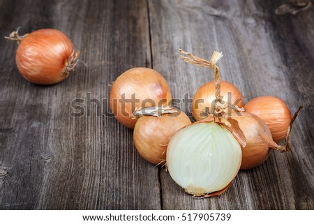 Fresh onions on a wooden background.