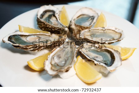 Fresh open oysters on plate - stock photo