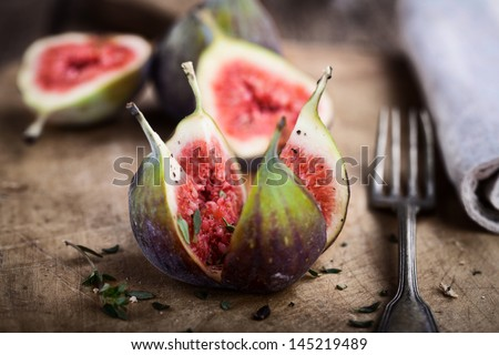 fresh opened figs on rustic wooden table - stock photo
