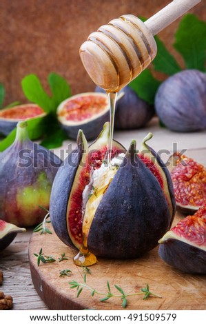 Fresh opened figs with cheese and honey on  wooden table.