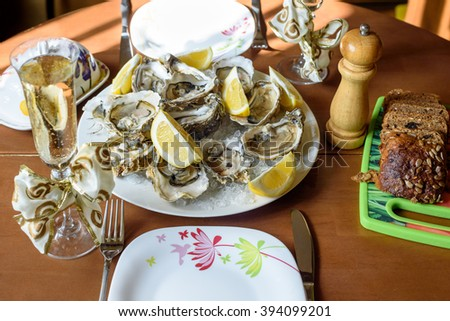 Fresh opened oysters on a plate of ice on a table with two glasses of champagne, brown bread and butter - stock photo