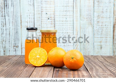 Fresh orange and juice on vintage wooden table background  - stock photo