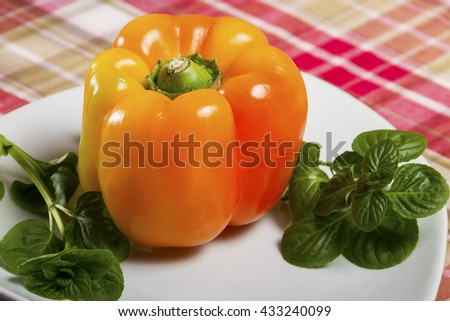Fresh orange bell pepper and basil served on a white plate on the table - vegetable, herb, curative, vegan food. - stock photo