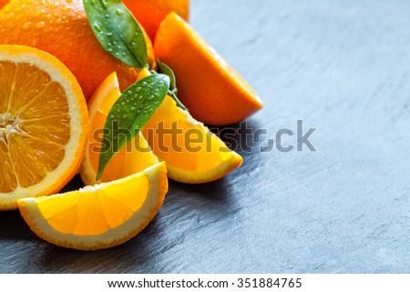 Fresh orange fruit placed on black stone. Copyspace for text - stock photo