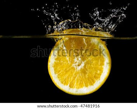 Fresh orange is splashing into the water on black background - stock photo