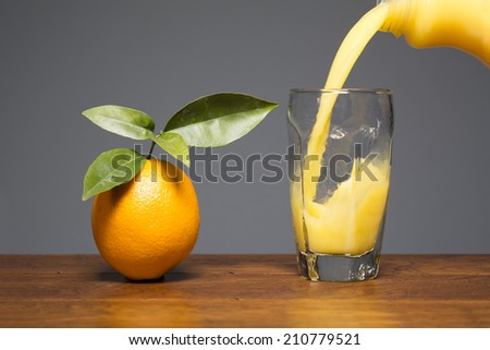 Fresh orange juice being poured into a drinking glass that sits next to a fresh, single orange.  - stock photo