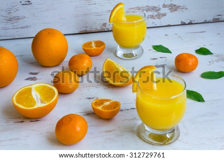 Fresh orange juice in a glass on the table and pieces of fruit. Oranges and tangerines. - stock photo