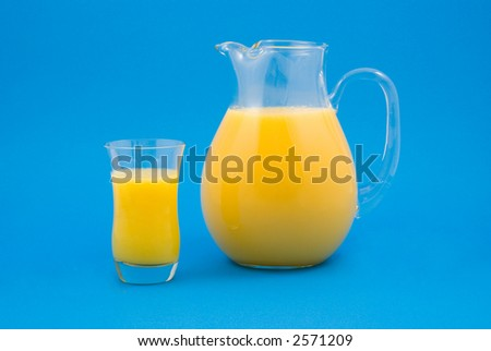 Fresh Orange Juice in Glass and Pitcher Isolated on Blue Background - stock photo