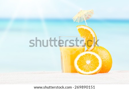 Fresh orange juice on sand with blue sky background, summer concept  - stock photo