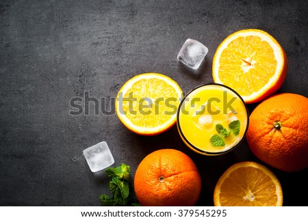 Fresh orange juice, orange slices, mint leaves and ice on dark background. Top view with copy space. - stock photo