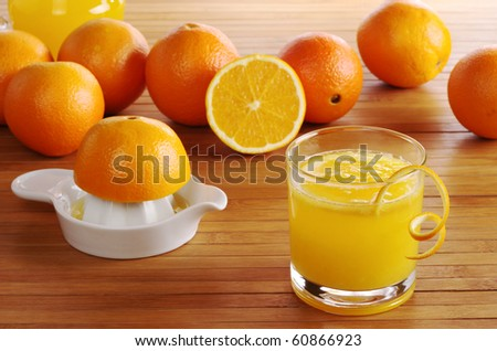 Fresh orange juice with orange juice squeezer and oranges on wooden mat (Selective Focus)