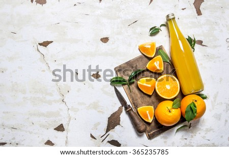 Fresh orange juice with oranges, leaves and a knife. On rustic background. Free space for text . Top view - stock photo