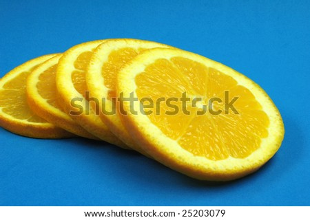 Fresh orange slices fanned out on blue background