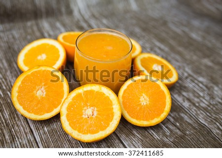 Fresh oranges fruits cuted in half and a glass of juice on a wooden background - stock photo