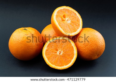 Fresh oranges on black background