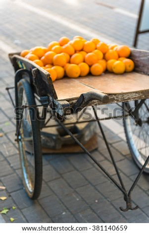 Fresh oranges on vintage wooden cart in the town. Shot with a selective focus