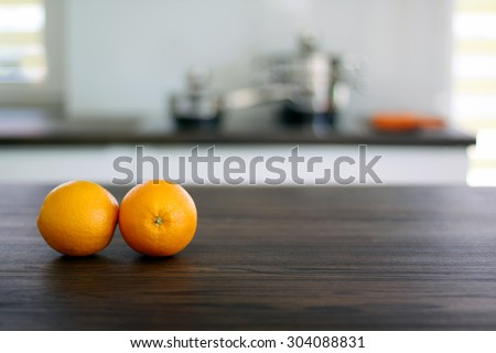 Fresh oranges on wooden tabletop in the kitchen - stock photo