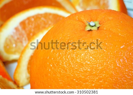 Fresh oranges served for breakfast. A focused orange next to some slices on a white plate. Copy space for editor's text. - stock photo