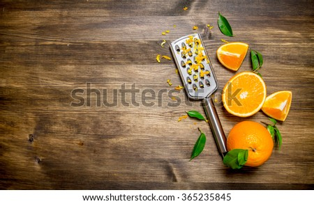 Fresh oranges with grater and zest. On a wooden table. Free space for text . Top view - stock photo