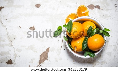 Fresh oranges with leaves in a bowl. On rustic background. Free space for text . Top view - stock photo