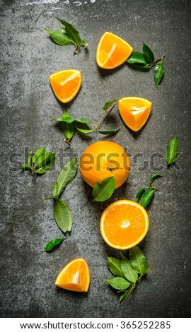 Fresh oranges with leaves. On the stone table. Top view - stock photo
