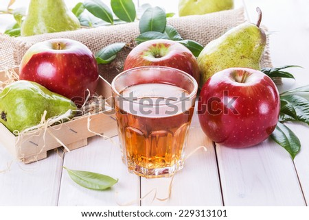 Fresh organic apples and pears and fresh juice over white wooden background - stock photo