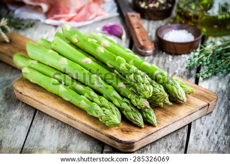 Fresh organic asparagus on a cutting board with Parma ham on a rustic table - stock photo