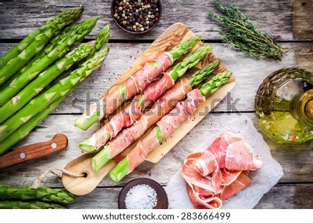 Fresh organic asparagus wrapped in Parma ham on a cutting board top view - stock photo