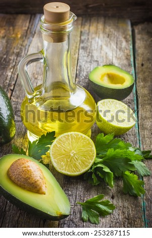 fresh organic avocado, lime, parsley and olive oil on  old wooden table - stock photo