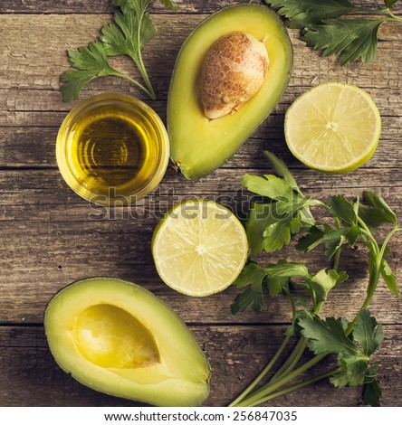 fresh organic avocado, lime, parsley and olive oil on  old wooden table, top view, square image, toned - stock photo