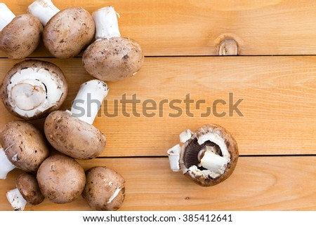 Fresh organic baby bella mushrooms for use as a savory ingredient in cooking and salads on a wooden kitchen table, viewed from above - stock photo