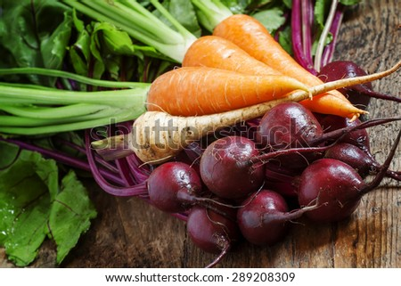 Fresh organic beets and carrots on old wooden table in rustic style, selective focus