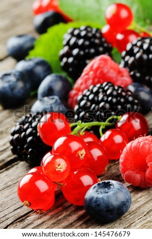 Fresh organic berries on wooden table - stock photo