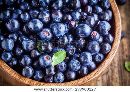 Fresh organic blueberries in a wooden bowl closeup