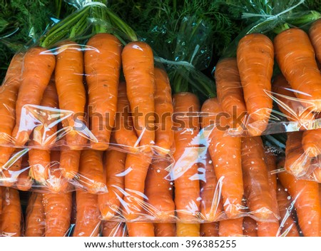 fresh organic carrot in the plastic bag on the local market.Thailand. - stock photo