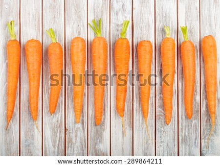 Fresh Organic Carrots isolated on wooden background - stock photo
