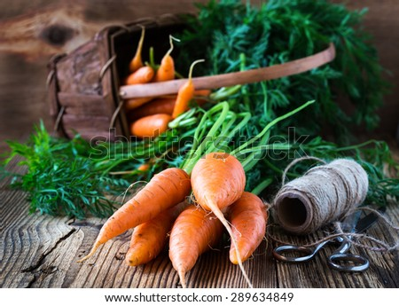 Fresh organic carrots on  rustic wooden background - stock photo