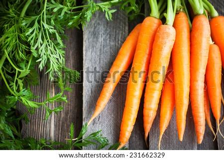 Fresh Organic Carrots on wooden background  - stock photo