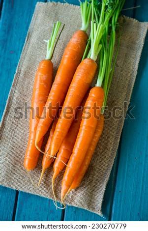 Fresh organic carrots on wooden table - stock photo