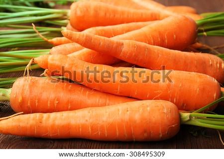 Fresh organic carrots on wooden table, closeup - stock photo