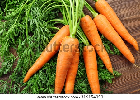 Fresh organic carrots with green tops on wooden table, closeup - stock photo