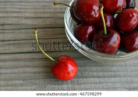 Fresh organic cherries berries in glass bowl on old wooden background.Selective focus.