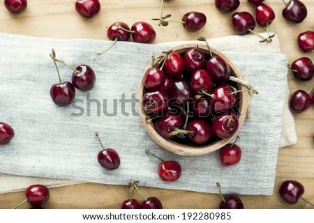 Fresh organic cherries on wooden background - stock photo