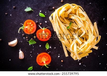 fresh organic cherry tomatoes and fettuccini with basil and garlic on a dark background - stock photo