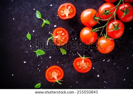 fresh organic cherry tomatoes with basil and sea salt on a dark background - stock photo