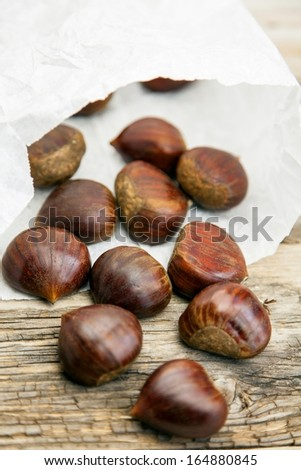 Fresh organic chestnuts in a white paper bag on wooden table