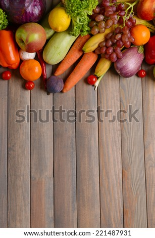 Fresh organic fruits and vegetables on wooden background - stock photo