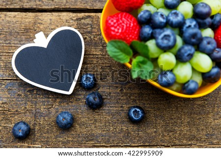 fresh organic fruits on wooden table, black heart with copyspace, flat lay - stock photo