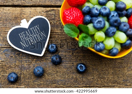 fresh organic fruits on wooden table, heart with text healthy nutrition, flat lay - stock photo